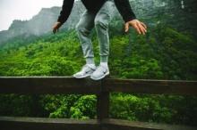 Trampolin Test - Junge balanciert auf Zaun